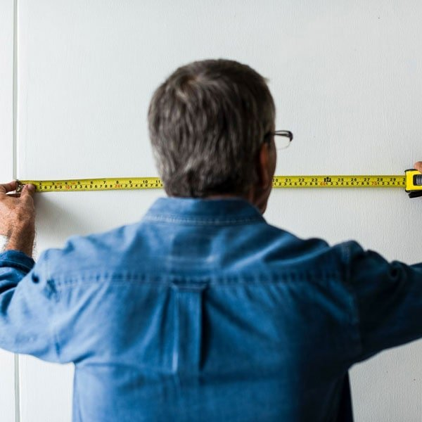 Man with blue shirt measuring with tape measure
