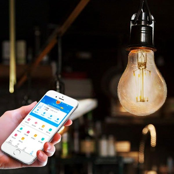 Person controlling Smart filament bulb with mobile app.